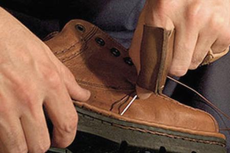 Cosido a mano de la suela de unos zapatos